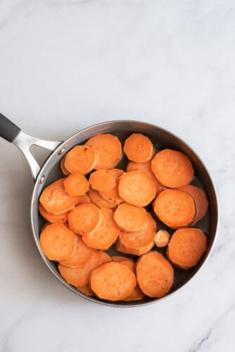 Peeled and sliced sweet potatoes in pot.