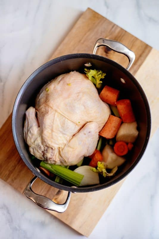 add ingredients into pot with whole chicken