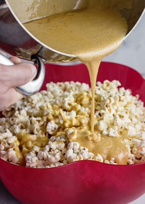 Pouring caramel over homemade caramel corn