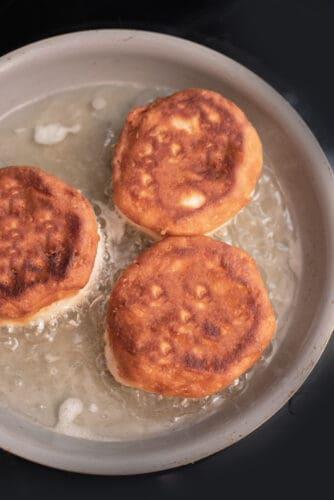 Golden brown mini Boston cream pies cooking in oil.