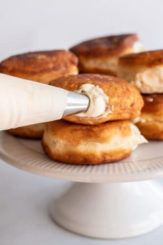 Piping filling into the mini Boston cream pies doughnuts.