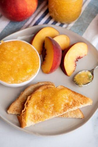 Peach jam on toast with peach slices on plate.