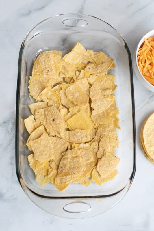 Tear half of your tortillas up into little pieces and layer them in the bottom of a 9x13 dish.