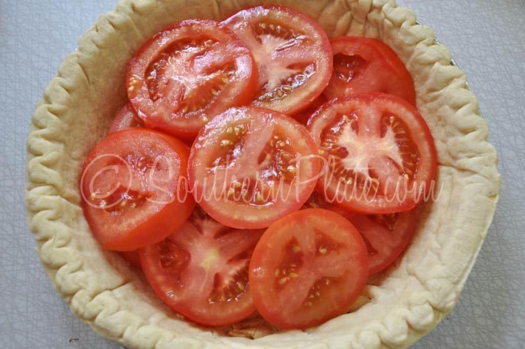 Adding tomato slices to pie.