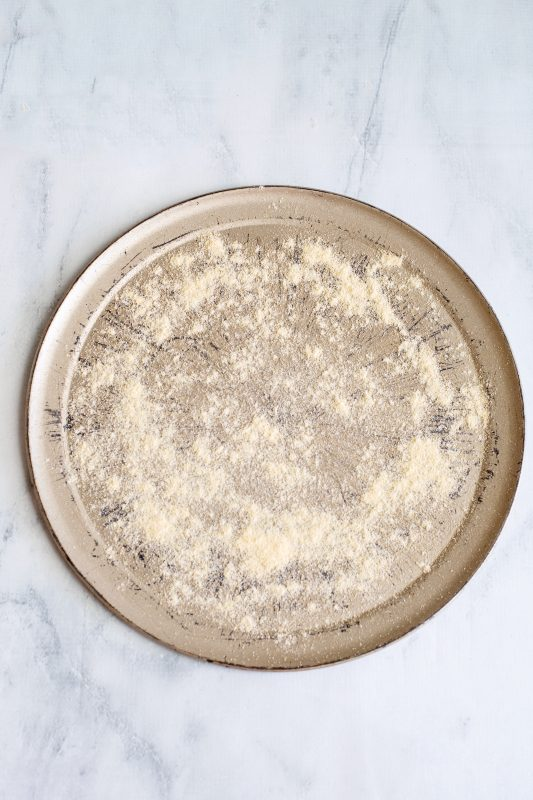 Sprinkle corn meal onto a pizza pan