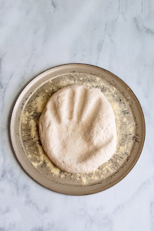 press your dough down on the pizza sheet