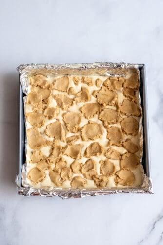 Broken cookie dough on wet ingredients in pan