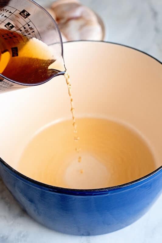 Pour vinegar into a dutch oven or deep pain