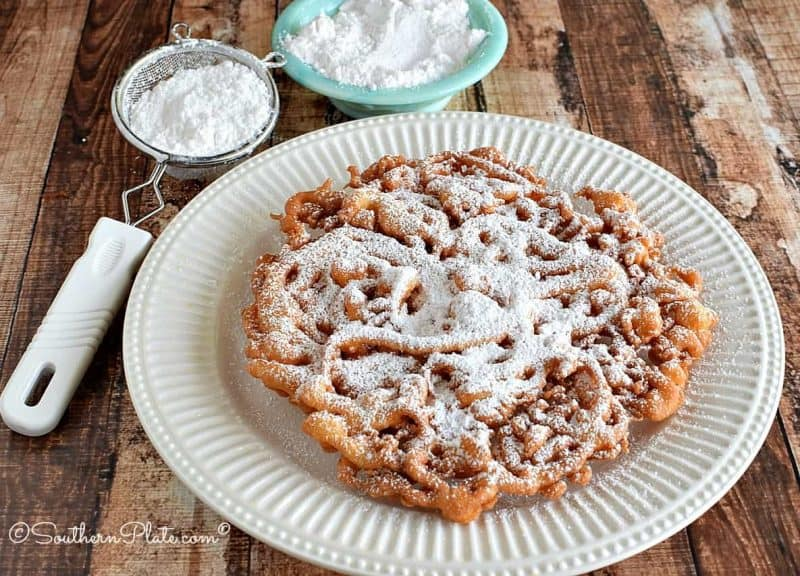 It's easy to make this large homemade funnel cake, covered in confectioner's sugar.
