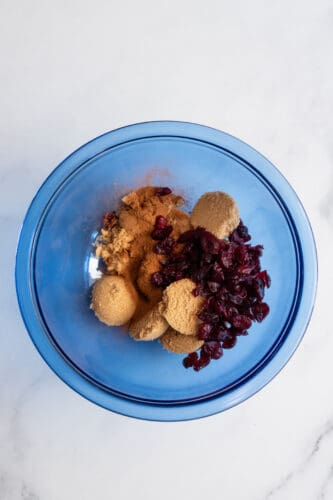 Brown sugar and cranberries on mixing bowl.