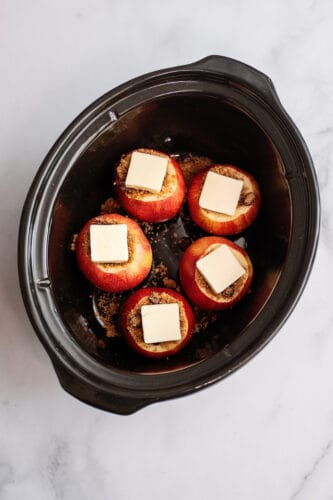 Each apple in slow cooker topped with pat of butter.