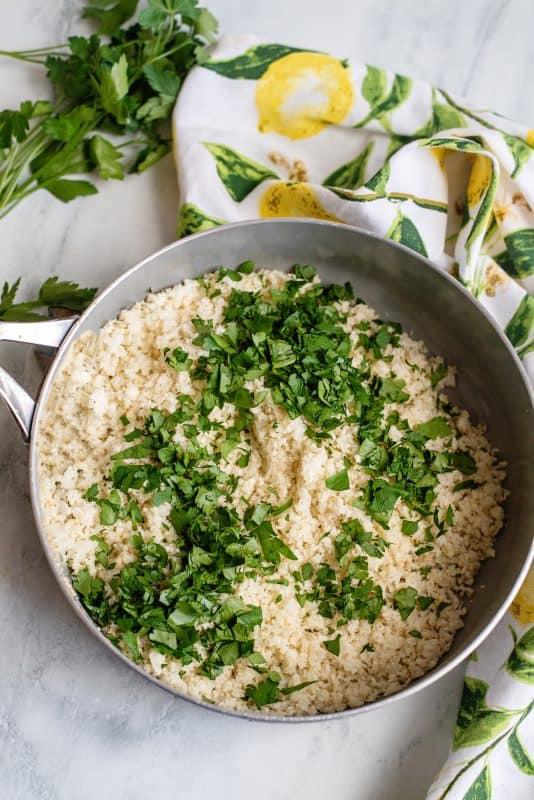 adding herbs to cauliflower rice