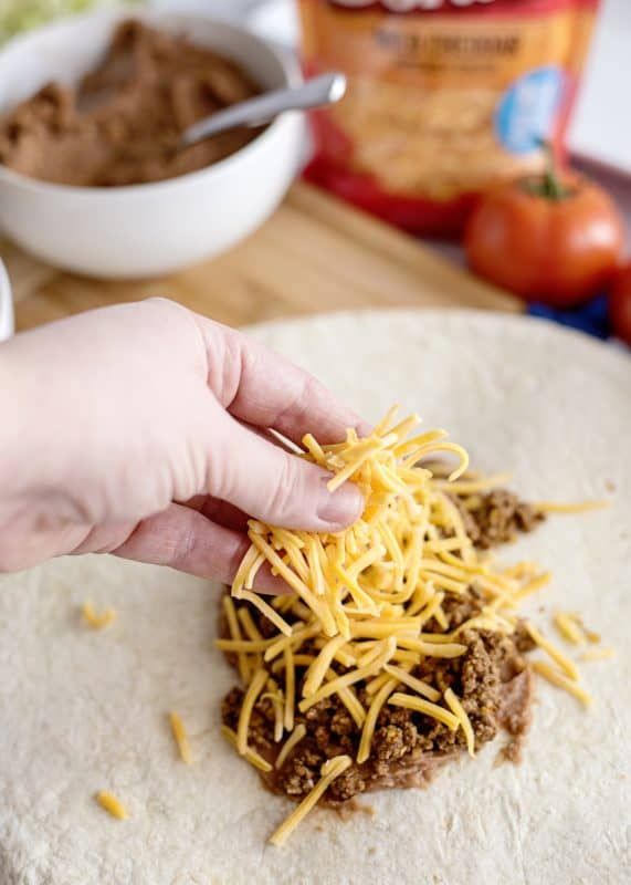 adding cheese to beef on tortilla
