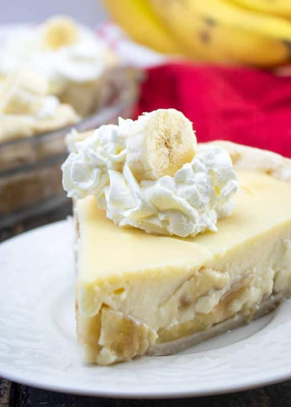 A slice of banana cream pie topped with whipped cream and a slice of banana