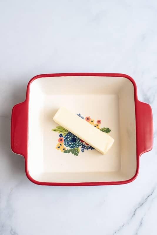 put butter in medium casserole dish