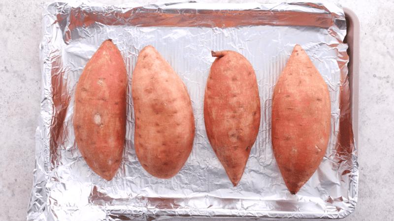 Sweet potatoes on foil-lined baking sheet.