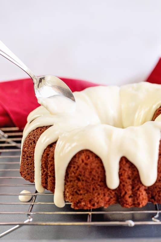 spoon frosting over bundt cake