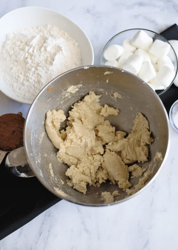 In mixing bowl cream together brown sugar white sugar and softened butter
