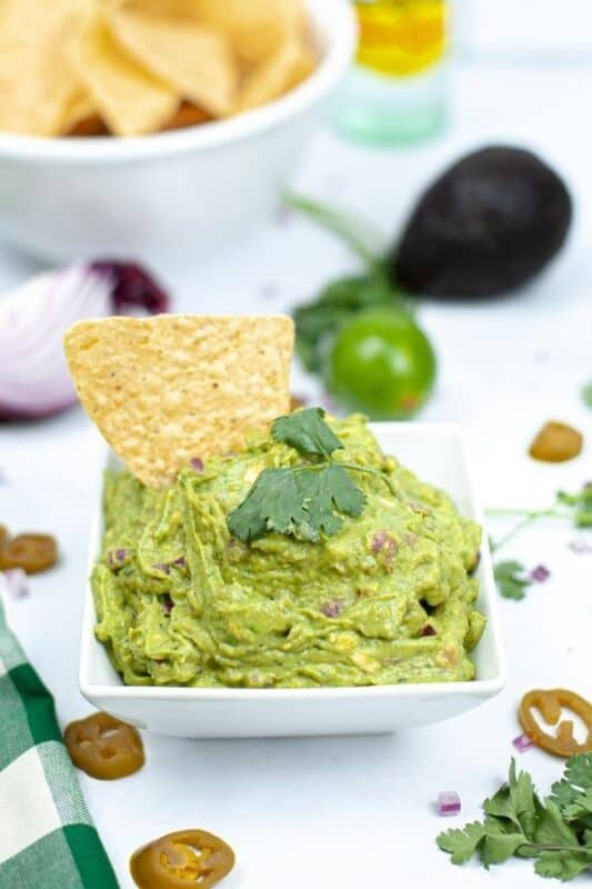 square bowl of guacamole on table