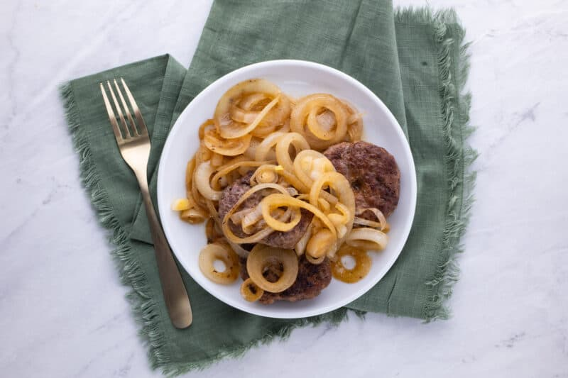 Hamburger steaks on plate with fried onions.