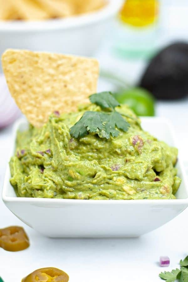 guacamole in a serving tray with chip in it