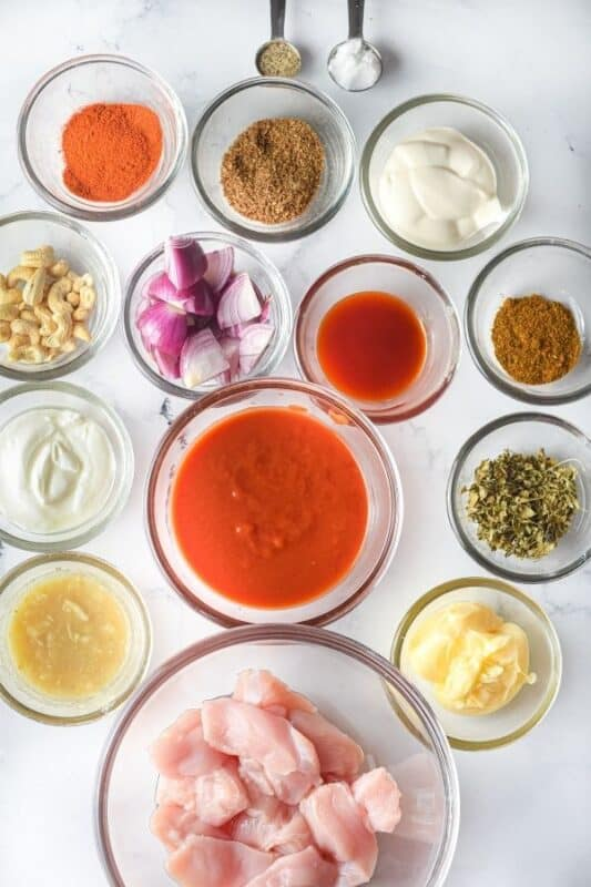 ingredients for butter chicken on marble counter