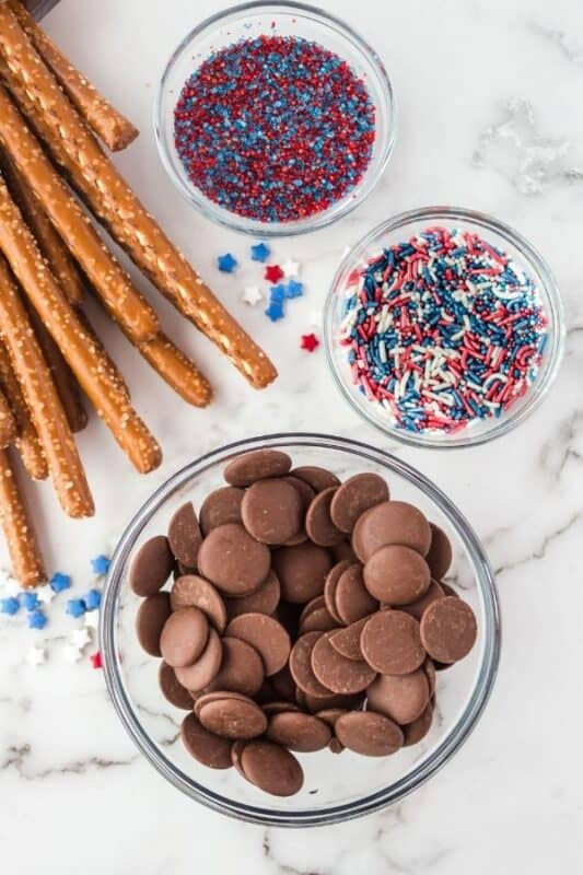 ingredients for chocolate dipped pretzels on counter with sprinkles in bowls