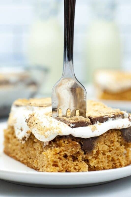 fork stuck into a slice of cake on plate