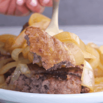 Forkful of hamburger steak with fried onions.