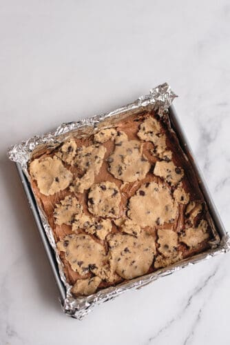 Cookie dough on top of cream cheese mixture in pan.