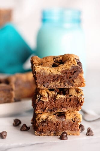 Three Chocolate chip cheesecake bars stacked on top of each other.