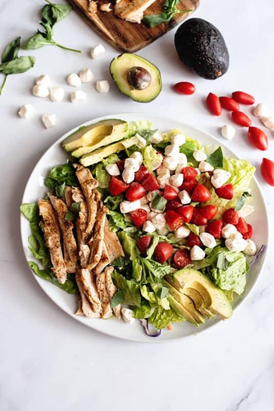 arrange avocado, mozzarella, cherry tomatoes and torn basil