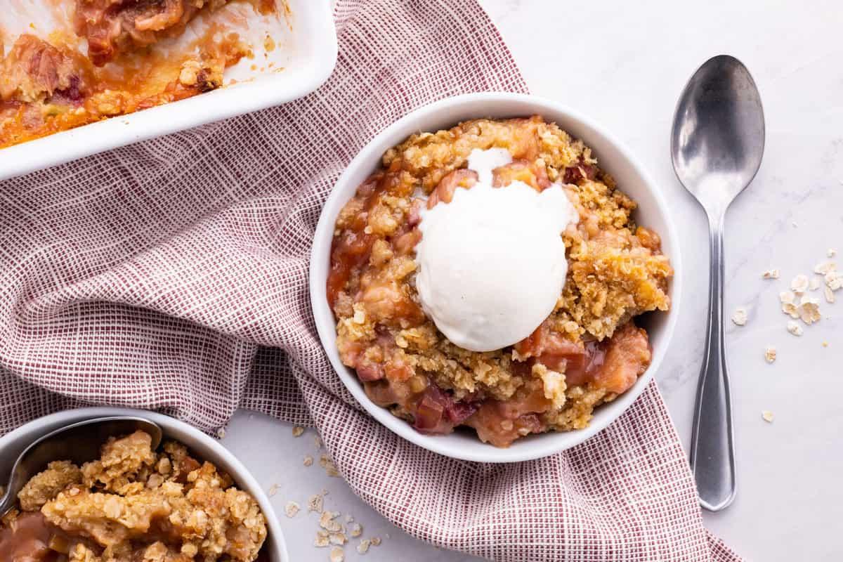 Rhubarb crisp topped with scoop of vanilla ice cream.
