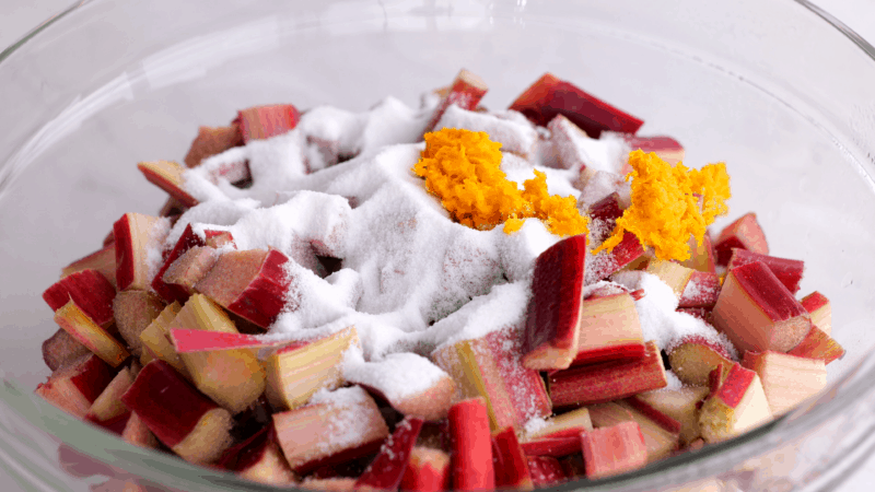 Rhubarb in bowl with sugar and orange zest