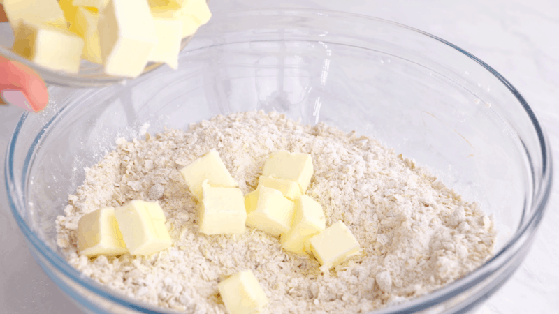 Butter slices on top of dry crisp topping ingredients.