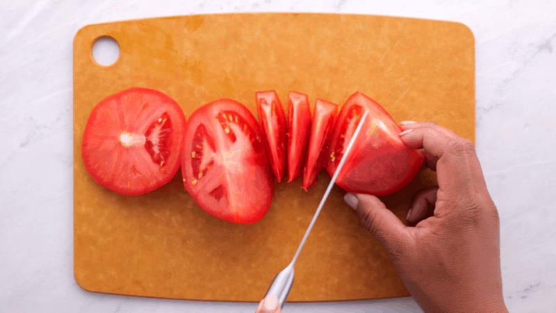 Cutting tomato into chunks.