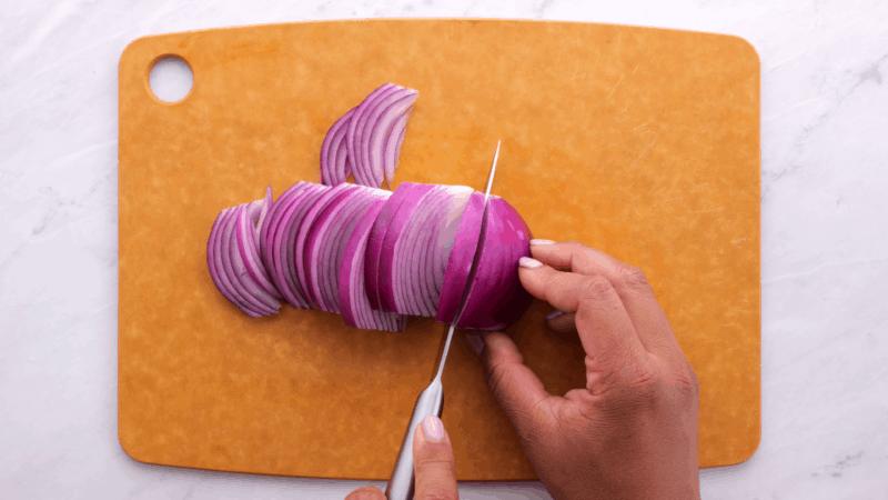 Cutting onion into large chunks.