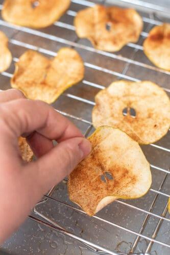 Flipping apple chips halfway through baking.