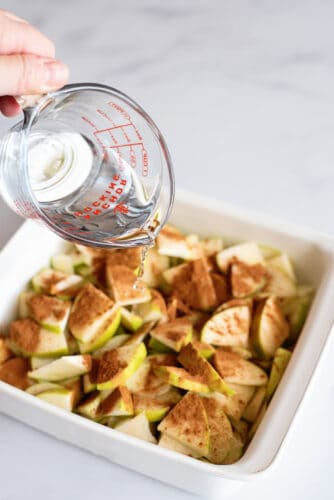 Pouring water over cinnamon-covered apples in baking dish.