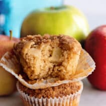 Two stacked apple muffins, with bite out of top muffin.