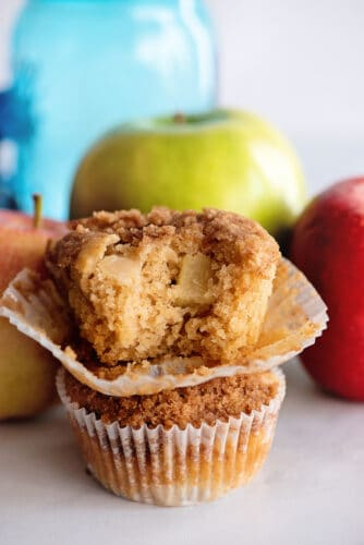 Two stacked apple pie muffins, with bite out of top muffin.