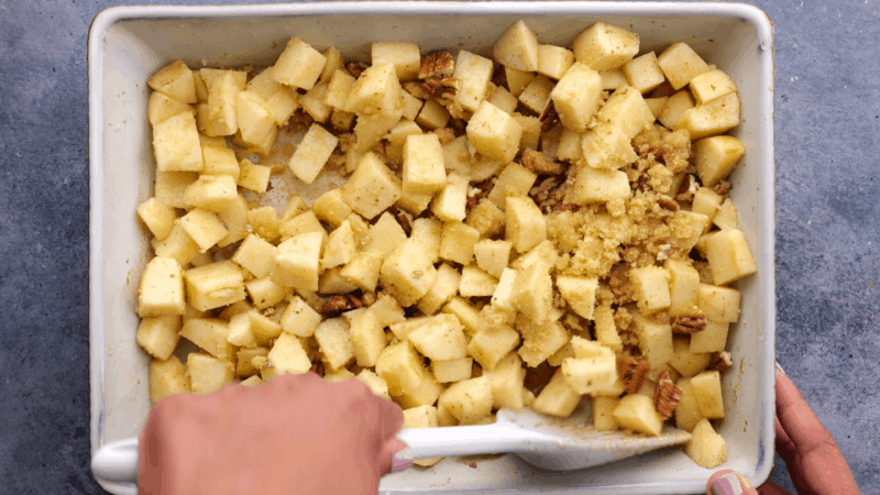 Mixing crumble topping into apple mixture.