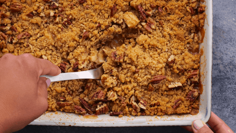 Scooping out portion of baked apple crumble.