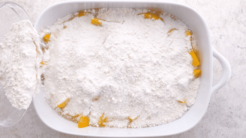 Cake mix sprinkled over peaches.