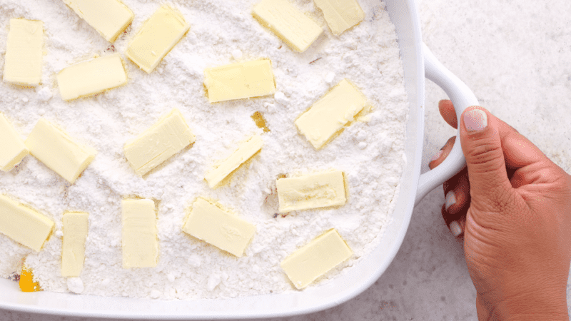 Sliced butter placed evenly over cake mix in baking dish.